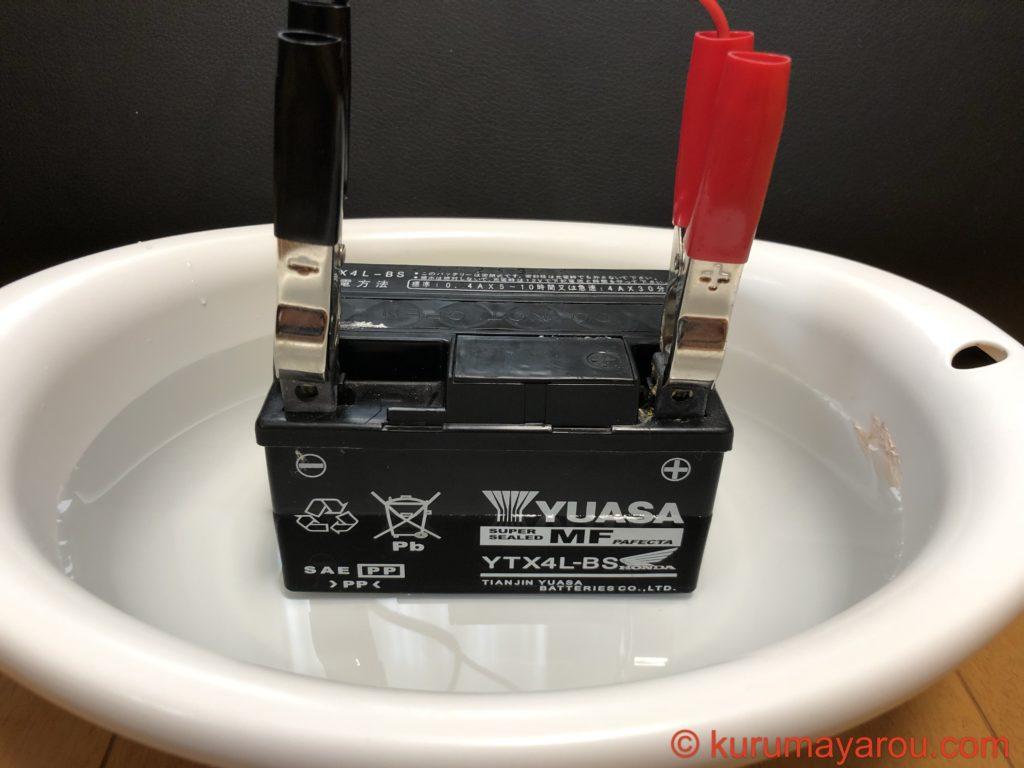 バイクバッテリーを水に半分程度浸す